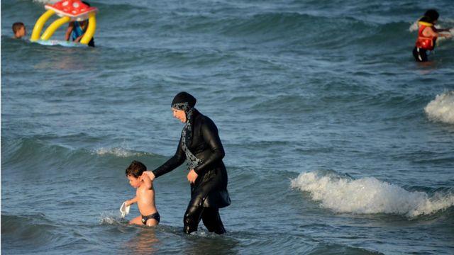 Una mujer se baña en una playa vistiendo un burkini.