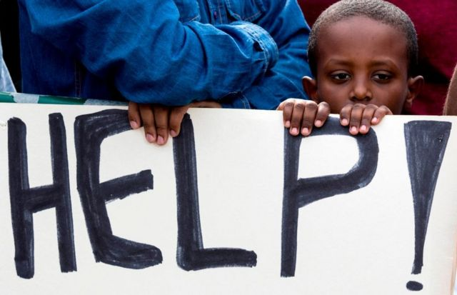 An African child stands behind a sign during a demonstration outside the Embassy of Rwanda in the Israeli city of Herzliya on February 7, 2018, against the Israeli government's policy to forcibly deport African refugees and asylum seekers to Rwanda and Uganda. Israel began on January 3 implementing a plan to deport by April tens of thousands of African migrants, mainly Eritreans and Sudanese, who entered the country illegally, threatening to arrest those who stay. Israel tacitly recognises that the Sudanese and Eritreans cannot be returned to their dangerous homelands, so it has signed deals with Rwanda and Uganda, which agree to accept departing migrants on condition they consent to the arrangement, activists say.