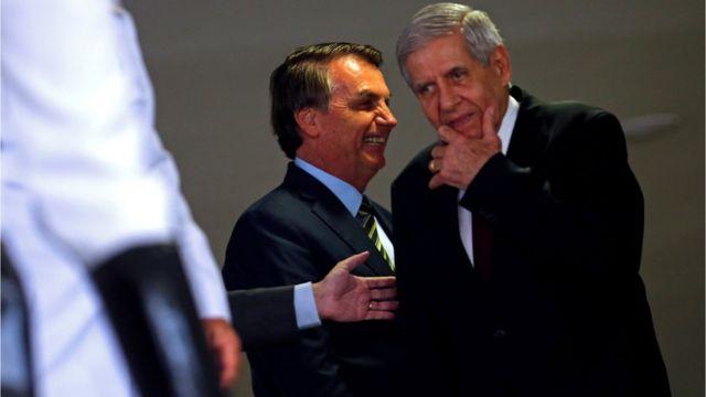 Jair Bolsonaro e Augusto Heleno conversam próximos em ambiente interno