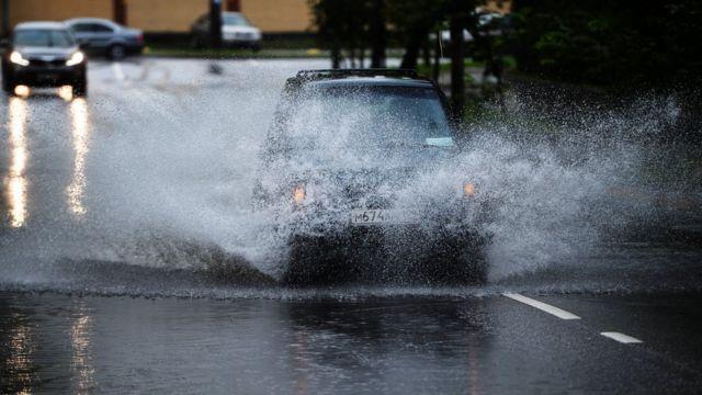 Автомобиль проезжает по луже, разбрызгивая воду