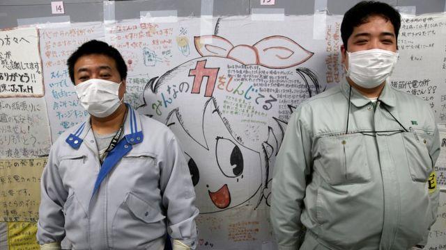 Dos empleados frente a una pared de mensajes de aliento.