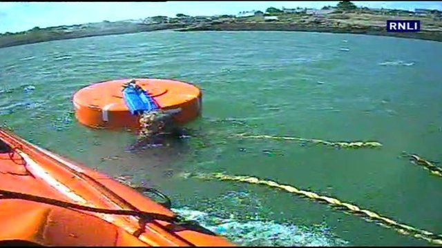 A 60-year-old man clings to mooring buoy in the water