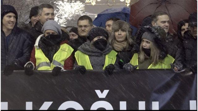 Demonstranti na čelu kolone uvijeni u šalove i kape zbog jakog snega