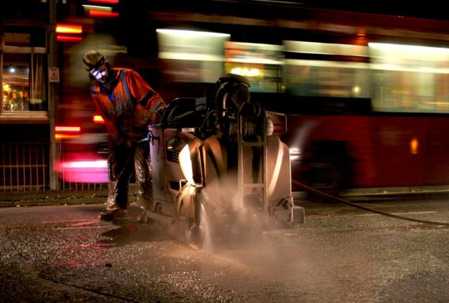 A construction worker works through the night as a red bus passes him by