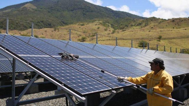 Homem limpa painéis solares na Costa Rica em 2015