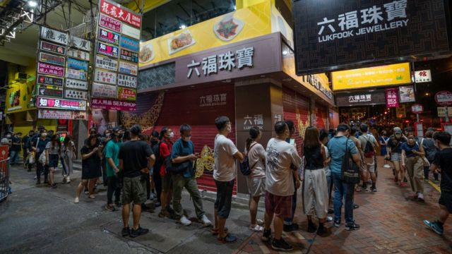 Supporters wait in line to purchase the final edition of the Apple Daily newspaper