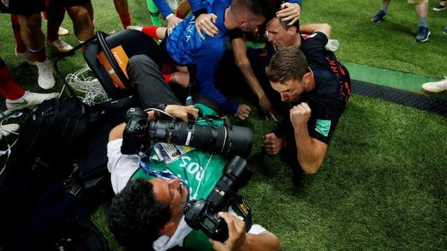 Photographer lying on the floor with football players