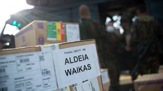 Caixa com aviso 'Aldeia Waikas' em pátio de decolagem, com militares e helicóptero no plano de fundo