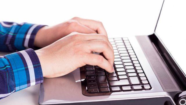 شخص يكتب على لوحة مفاتيح جهاز الكمبيوتر المحمول