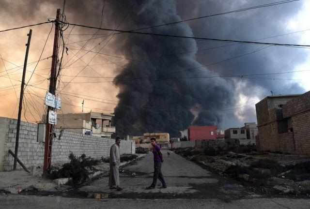 رجال محليون إثر إشعال مسلحي تنظيم الدولة الاسلامية النار في أحد آبار النفط قبل عملية الموصل، في القيارة يوم 21 أكتوبر / تشرين الأول 2016.