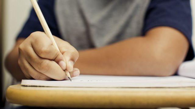 Menino escreve com lápis em folha
