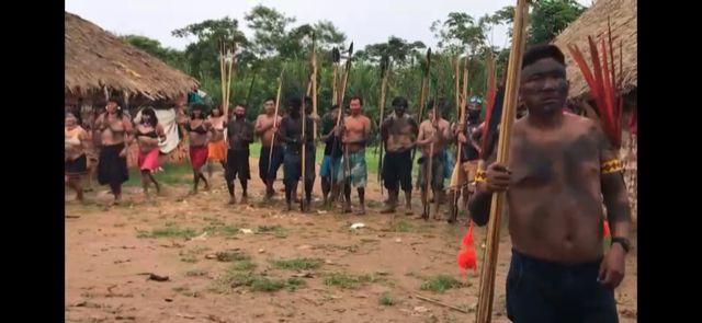 Tribo reunida em círculo em área externa
