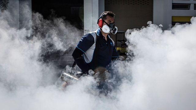 蚊が繁殖しやすい場所を燻蒸消毒するシンガポールの衛生部局職員(先月3日)