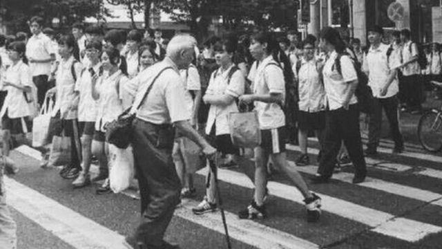 横断歩道で女子学生の集団とすれ違うお年寄り