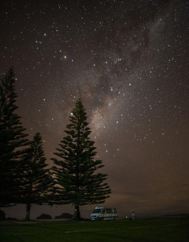 شاحنة تخييم متوقفة تحت سماء مليئة بالنجوم