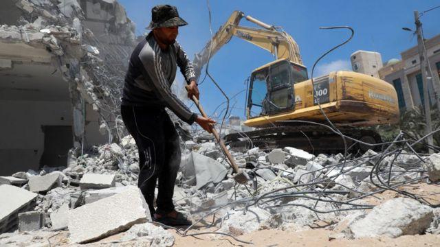 عمال فلسطينيون يزيلون أنقاض المباني التي دمرها القصف الإسرائيلي خلال الصراع بين إسرائيل وحماس في مايو/ أيار
