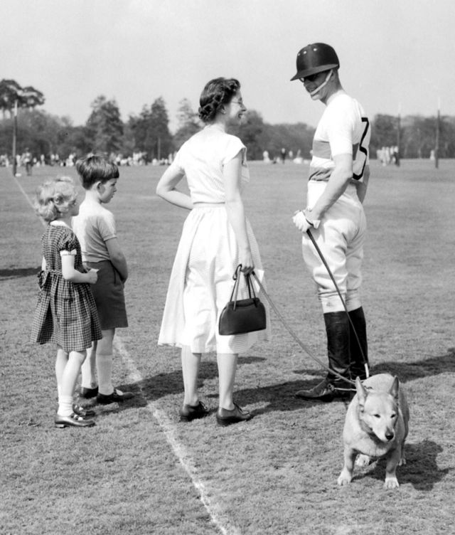 The Queen, with one of the Royal corgis, chats with polo-playing Prince Philip at Windsor Great Park