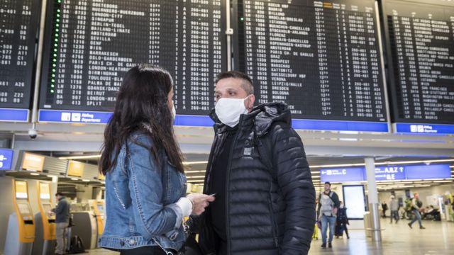 Gente en aeropuerto con tapaboca.