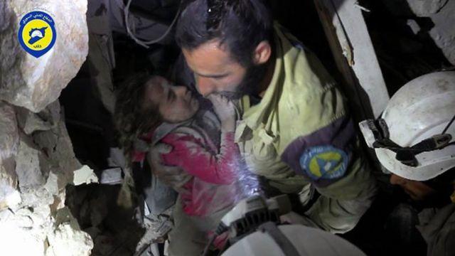 Rescatistas ayudan a un niño sirio entre los escombros de Alepo