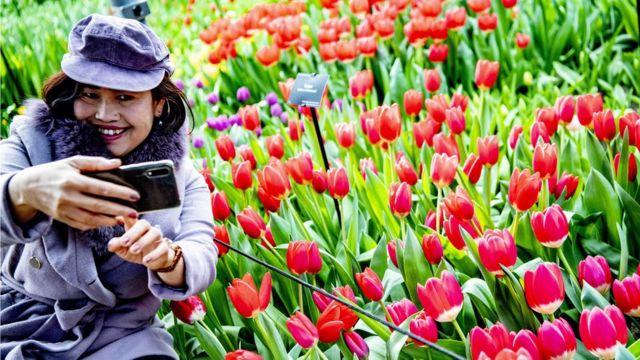 Lalelerle fotoğraf çektiren turist