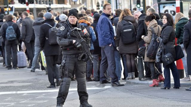 バスを待つ人の列を武装警官が警備した
