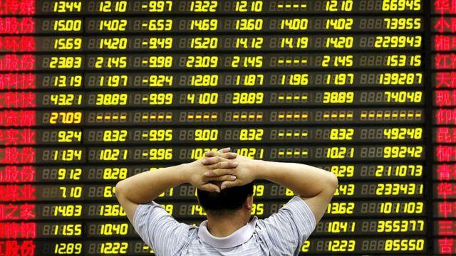 Homem com as mãos na cabeça observando painel com preços de ações