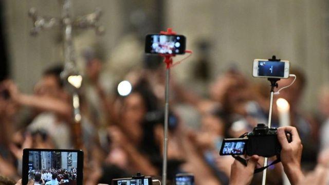 Teléfonos en palos de selfies tomando fotos de una cruz