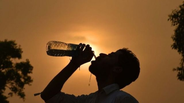 A man drinks water from a bottle in front of a hot Sun