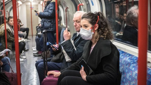 woman in mask on london underground