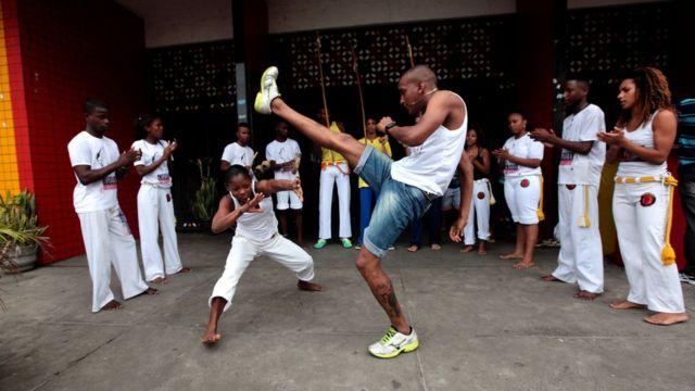 Jovens jogam capoeira