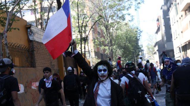 Un hombre con la cara pintada de blanco sosteniendo una bandera de Chile.