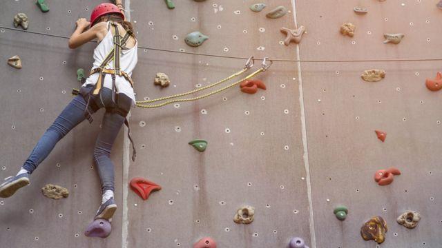 Una mujer escala en una pared