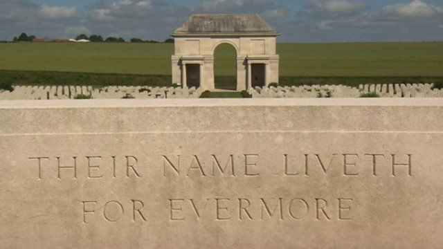 Graves of fallen soldiers behind a memorial