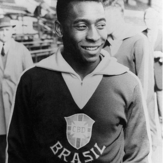 Em foto preto e branco, Pelé sorri, com casaco do Brasil