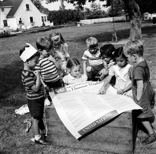 Crianças com um exemplar gigante da Declaração