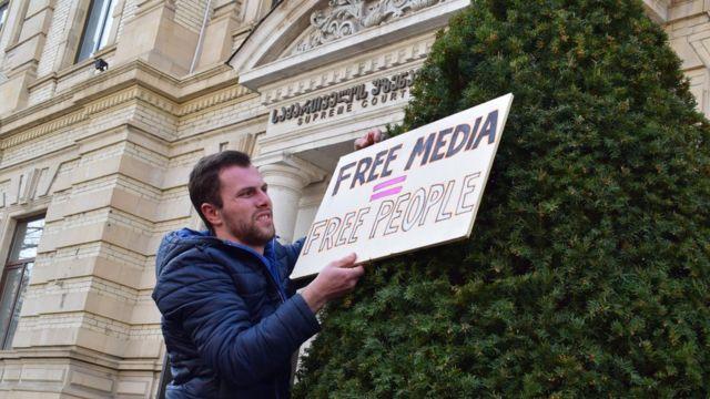 Мужчина вешает плакат на елку у здания Верховного суда Грузии