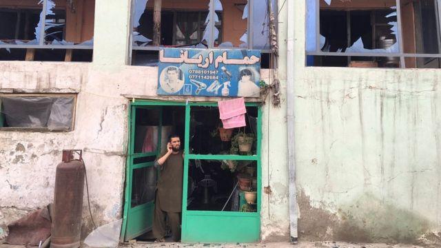 爆発の被害に遭った自分の店舗内に立つ男性(19日)