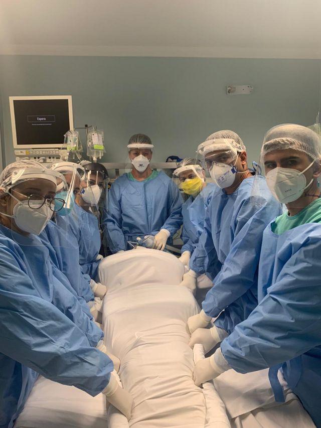 Equipe médica posa para foto com corpo de Raquel envolto em um tecido para que possa ser colocado de bruços