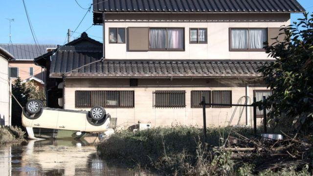 A car lies upside down following heavy flooding, on July 8, 2018 in Kurashiki near Okayama, Japan