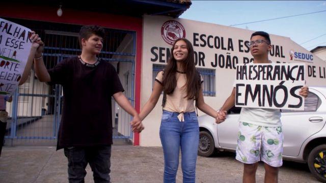 "Ana (tengah) dan Bruno (kanan) dengan tanda bertuliskan ""Ada harapan di dalam kita"""