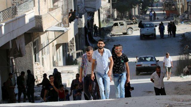 Residentes caminan por un barrio de Alepo.