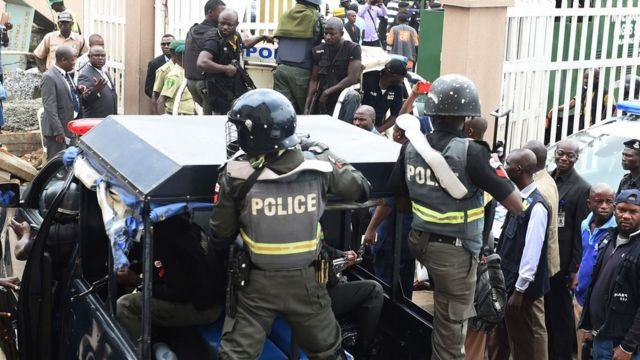 Nigerian ant-riot police officers escort a suspected kidnap kingpin to prison after he was arraigned at the Lagos State High Court
