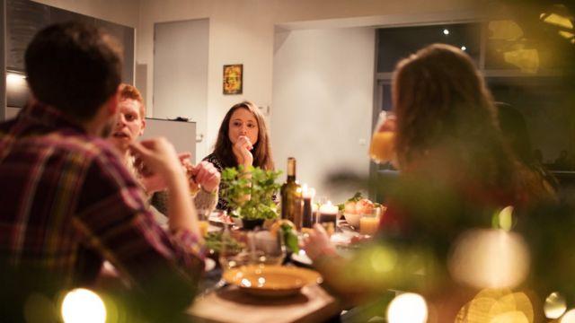 Quatro pessoas discutem sentadas à mesa