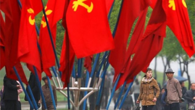 "People walk behind party flags placed near April 25 House of Culture, the venue of Workers"" Party of Korea (WPK) congress in Pyongyang"