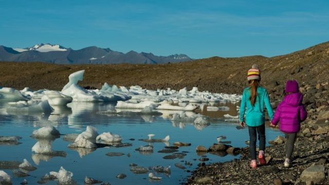 Two children walk by melting glaciers in Iceland