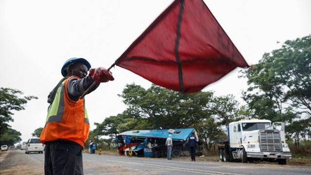 ผู้ชายกำลังโบกธงแดงข้างถนน