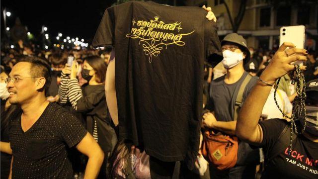 """ผู้ชุมนุมชูเสื้อที่มีข้อความสกรีนว่า """"รอยัลลิสต์ มาร์เก็ตเพลส"""""""
