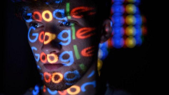 Joven con el logo de Google reflejado en la cara.