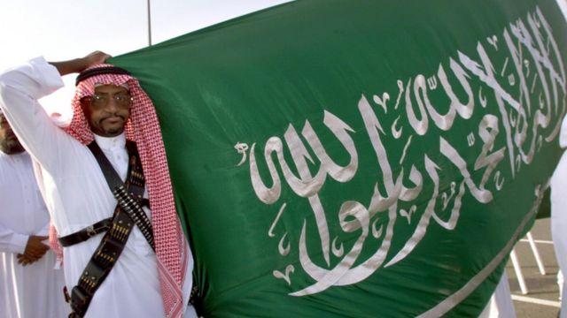 A Saudi policeman holds up a flag