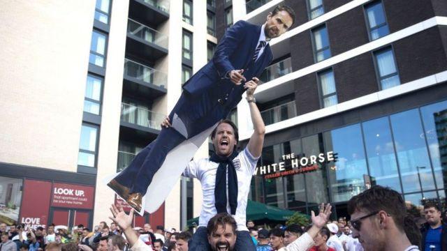 Un supporter devant le stade de Wembley porte une pancarte à l'effigie du manager de l'Angleterre, Gareth Southgate
